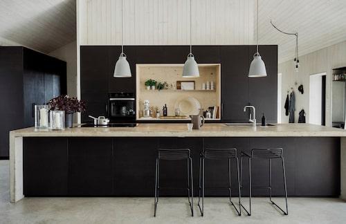 Såväl golvet som köksöns arbetsskiva och sidostycken är gjutna i betong. På köksön har ytan vaxats för att stå emot fettfläckar och väta vid matlagning. Nischen mellan kyl, frys, ugn och skafferi är en kombinerad arbets- och avställningsyta tillverkad av plywood, som lackats för att skyddas mot smuts. Köksstommarna är från Ikea och de svarta fronterna är egentillverkade. Ugn, Miele, vattenblandare Mora armatur. De svarta barstolarna från Massproducktions smälter fint in i köksöns front. Taklampor Caravaggio, Fritz Hansen, ljuslyktor i glas, Walles & Walles.