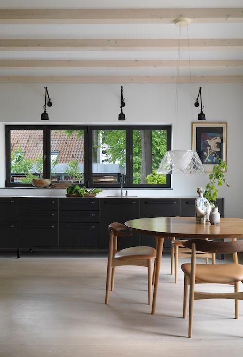 """Vipp har gjort det mattsvarta modulköket av pulverlackat stål. """"Vi gillar att köket är som en möbel, ingenting sitter fast i väggen."""" På väggen litografi av Georges Braque, och lampor från Vipp. Ekhyllor och matbord från Københavns møbelsnedkeri, stolen är Cow horn chair av Knud Færch, Warm nordic."""
