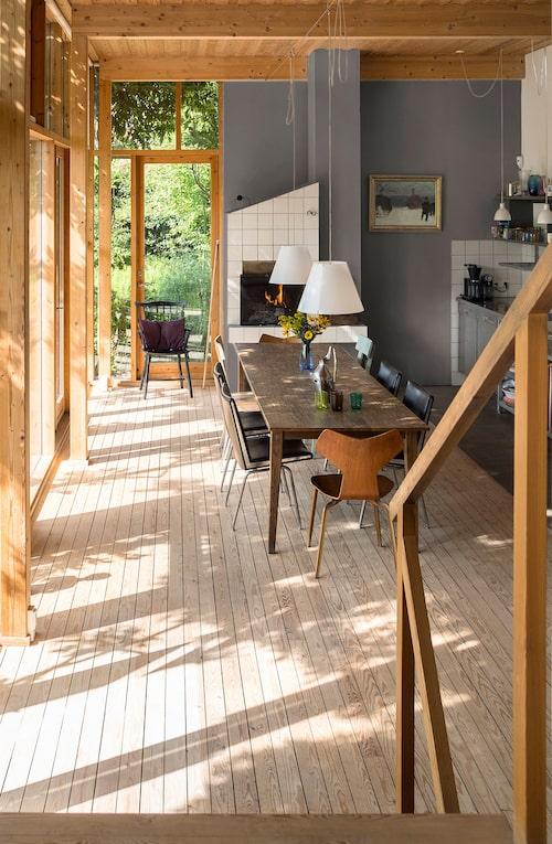 Allt naturträ och den öppna spisen i bordshöjd ger trivsel och värme. Trägolvet har gummifogar och ligger i nivå med terrassen utanför.