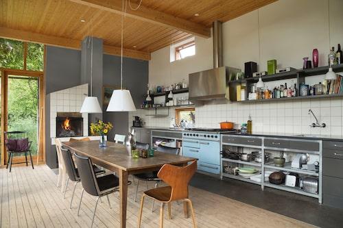 """Köksannexet är inrett med trä, glas, stål, betong och enkelt vitt kakel. Mycket industrikänsla – med Falconspisen, fläktkåpan och de öppna hyllorna. """"Vi bara älskar vår blå spis, den har två ugnar och är så effektiv!"""" På bordet den ikoniska HK-kannan, formgiven av Henning Koppel för Georg Jensen."""