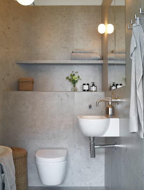 """Anna gillar inte kommoder och designade själv lösningen med ett inbyggt badrumsskåp som döljs bakom spegeln. Som kontrast till gråbeige sten och kromade rör tyckte Anna att tvättkorgen i jute gav lite liv. Handfat från Globo under vägghängd kran i modell Meta från Dornbracht. """"Badkaret, toalettstolen och handfatet är från tre olika leverantörer, alla är valda efter sin fina ovala form."""""""