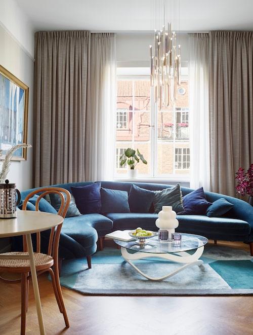 """Vid fönstren finns takhängda gardiner liksom i sovrummet. Rummet domineras av den generösa blå soffan som Anna köpte av en vän, och kommer från en nu nerlagd butik. """"Soffan gör mig glad, den är lite dekadent, inte så svensk och lagom."""" Asymmetrisk blockmönstrad matta från brittiska made.com."""