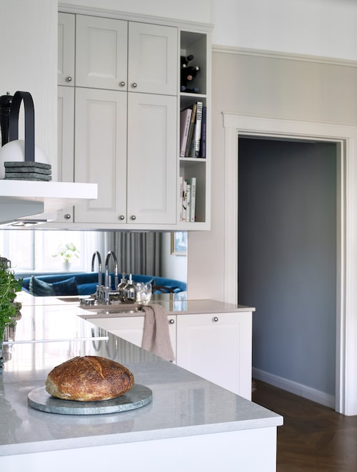 Köksluckornas ljusgrå färg, som också är genomgående för hemmets alla snickerier, är lite ljusare än den grå väggfärgen. Allt för att ge illusionen av sömlöshet.
