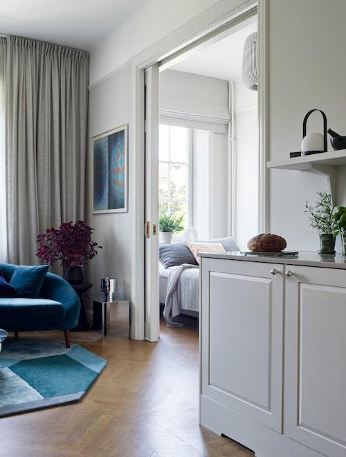 """Lägenhetens genomgående ekparkett kallar Annas inredare Madeleine för """"parisiska golv"""". """"Det låter så härligt, vi använde en lite mörkare hårdvaxolja på dem."""" Sovrummets skjutdörrar är i original. Hissgardinen är fäst i taket och specialsydd i tyg från Astrid."""