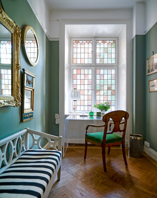 Jugendbonanza i hallen med det vackert blyinfattade fönstret. Stolen och soffan är arvegods. Plexiglasbordet är måttbeställt. Papperskorg från Svenskt tenn.