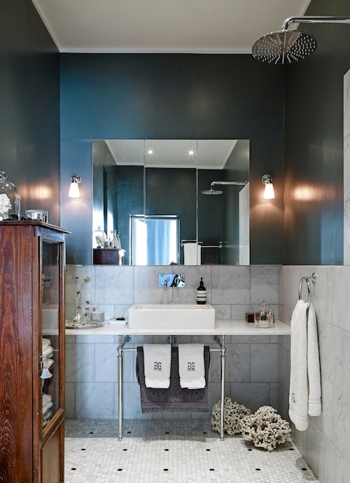 I badrummet finns hexagonmosaik i marmor på golvet, och carraramarmor på väggen. Övre delen av väggen är målad i kulören Down pipe från Farrow&Ball. Handfat, Duravit, benställning till tvättstället, Burlington. Inbyggda blandare och dusch, Tapwell. Vägglampor från Antikmagasinet. Notskåpet med handdukar är ett antikfynd.