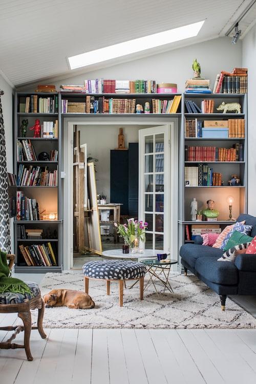 Bobo har själv snickrat bokhyllan som ramar in pardörrarna mellan vardagsrummet och ateljén. Soffan i howardstil är från The sofa store, ryamattan Tanger från Ellos och soffborden från Artilleriet. Stämningen sätts av Josef Frank-pallen, 30-tal, och den antika fåtöljen.