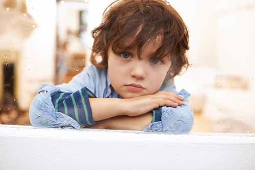 Portrait of an unhappy-looking little boy sitting and looking out a window on a rainy day