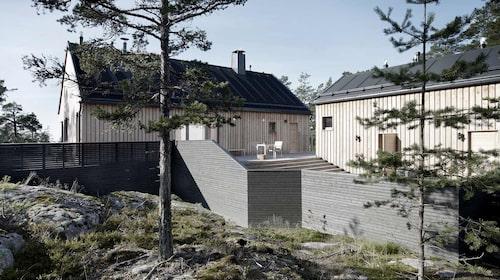 Husen är byggda av lärkträ som har en naturlig rötbeständighet och knappt kräver något underhåll. Träet får med tiden en ljusgrå, silverskimrande nyans. Till höger ligger bastubyggnaden.
