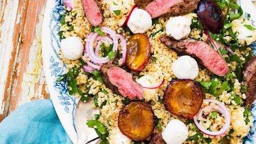 Lägg salladen på ett fat och toppa med lammfilé och plommon.