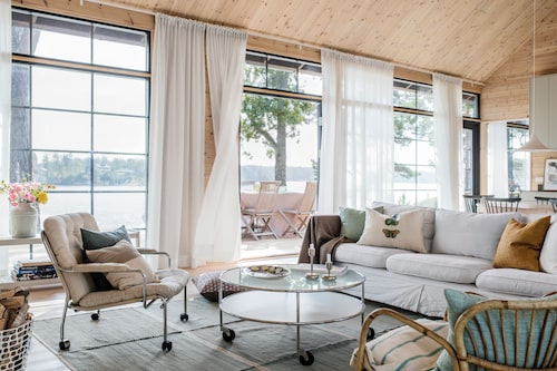 Genom gardinfladdret skymtar Blidösund. Gardiner och stänger, Ikea. I förgrunden fåtöljen Karin av Bruno Mathsson, soffbord av Gunilla Allard, soffa från R.o.o.m. Kudde med fjärilsmotiv, Designers Guild.