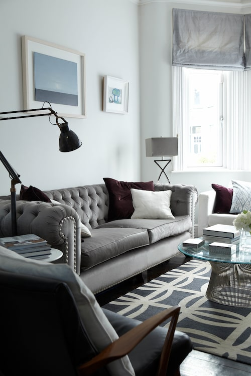 Skön sammet i soffa och kuddar mjukar upp i det sobert färgsatta vardagsrummet.