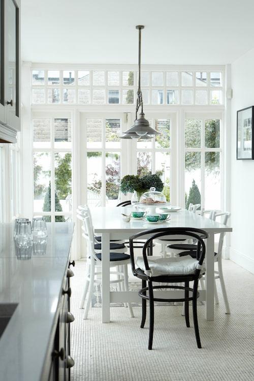 Köket har ett fantastiskt mosaik-golv – lägg märke till mönstersättningen under matbordet! – och de många fönstren och verandadörrarna gör att hela köket fylls med ljus.