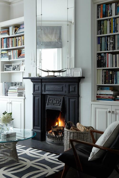 Vardagsrummet är inrett i grafiskt svart och vitt, med välfyllda bokhyllor och en värmande brasa i den vackra gamla eldstaden blir intrycket mysigt ombonat.