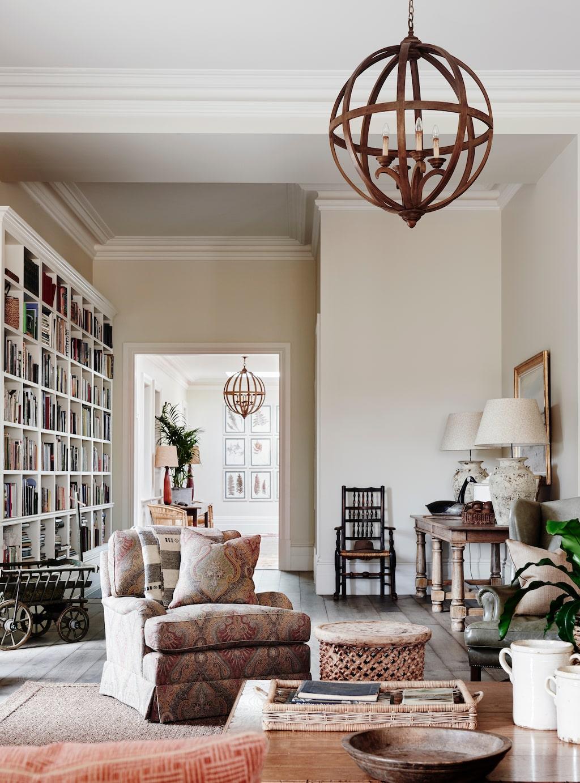 Passagen mellan hallen och vardagsrummet hyser en bokhylla som nästan går ända upp till tak.