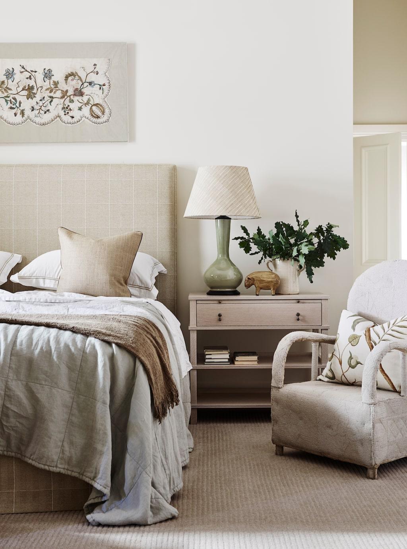 Sovrummet går i elfenbensvita nyanser. Sänggavel i det rutiga tyget Blakeney check i färgen Sand, Colefax and Fowler.