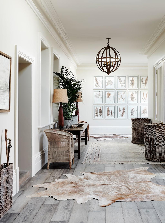Liksom vardagsrummet har hallen afrikanska bordslampor och en majestätisk klotlampa, Cromwell. Naturtemat fortsätter här med en större samling inramade ormbunkar. Mattan och kohudarna är vintage.