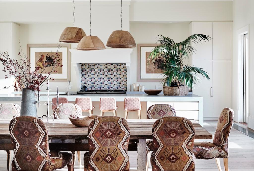 Det stora matbordet binder samman kök och vardagsrum. Över köksön hänger lampor tillverkade av gamla olivkorgar för att göra takhöjden mer mänsklig. Konst med fjäderfän av Sarah Bishop.