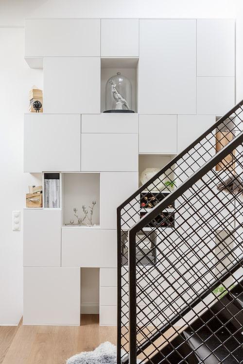 Det vita hyllsystemet byggde Jenny och Pelle av olika köksskåp från Ikea. Några tomrum har lämnats för vinflaskor, magasin och andra saker. Glaskupan kommer från Åhléns och fågeln inuti från Artilleriet. Silverljusstake från Market 29.