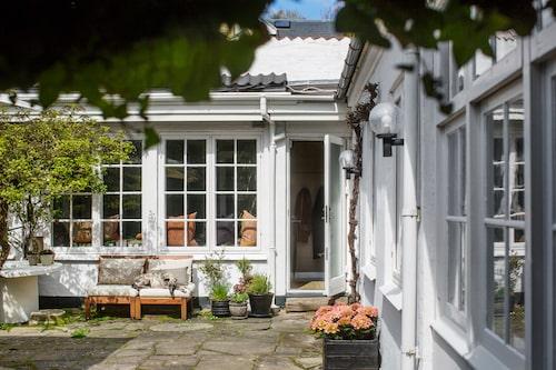 Den inbjudande innergården med den vackra gamla stenläggningen ramas in av den vita fasaden.