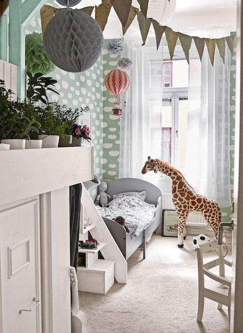 Barnrummets väggar har tapet från Ferm living. Växasäng från Ikea, luftballong från Artilleriet och giraff från Melissa & Doug.