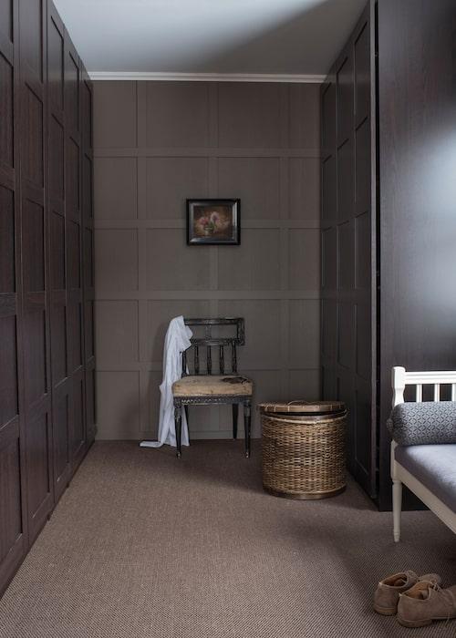 Heltäckningsmattan rinner över golvet från sovrummet in till Fredriks walk-in-closet. Stolen stod i grannens förråd och blir här ett oväntat utropstecken mot allt det moderna.