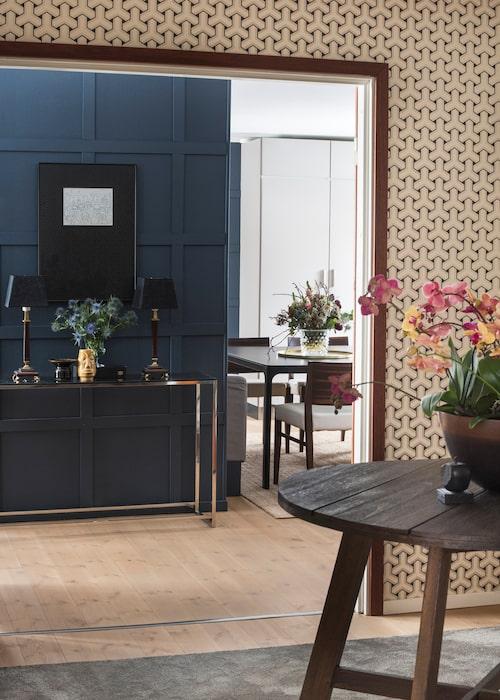 Den kvadratiska hallen med tapeten Trifid från Osborne & Little. Teaklisten runt öppningen är fin som kontrast. På det gamla trädgårdsbordet står en kruka av Rina Menardi, italiensk keramiker.