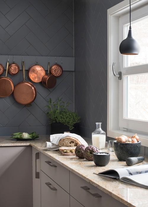 Fredrik älskar att laga mat och tillbringar många timmar i köket på sin fritid. Väggen är klädd med grå kakelplattor som lagts i fiskbensmönster. På listen hänger vackra kopparkärl. Köket kommer från Kvik, bänkskiva av venetiansk granit, något varmare i tonen än marmor.