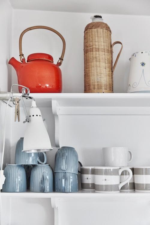 Öppna hyllor. Lättåtkomliga köksprylar hör till det enkla sommarlivet. Den röda tekannan är arvegods och den flätade termosen köpt i en kinesisk butik. Klämlampa från Ikea
