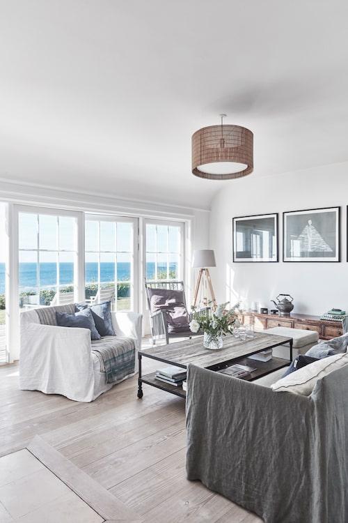 Havet i blickfånget. Från vardagsrummet dras blicken genast till den extraordinära havsutsikten. Inredningen är nedtonad, varför tävla? Bekväma sittmöbler, mjuka kuddar och skönt linnetyg dominerar. Fåtöljen och soffan med vitt respektive grått överdrag är från Gervasoni, och soffbordet från Casa shop.
