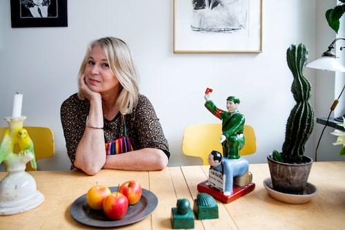 """Vid köksbordet, Bruno Mathssons Maria flap, i björk, Helena sitter nyss hemkommen från en litteraturkonferens i Kina. Där köpte hon statyetten på loppis. """"Jag tycker den är intressant för den är så hemsk."""" Undulatljusstake i keramik, Ingela Karlsson. Snäckorna har Ingvar Storm, programledaren från Spanarna, gjort i gjutformar."""