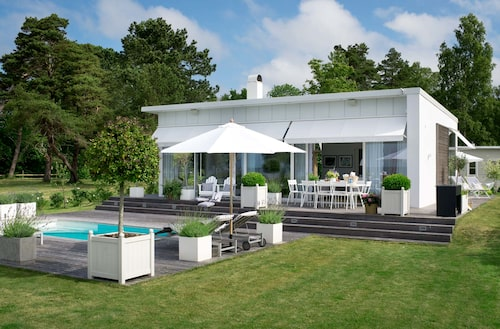 """Huset i glas och sten är ritat av Caroline Endre och arkitekt Richard Hellgren. Trädäck och andra detaljer i lärk. """"Jag var ute efter en beachhouse-känsla"""". På tomten finns också gästhus och bastu i lärkträ."""