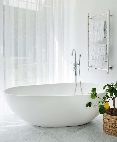 I badkaret från Agape, modell Spoon, kan nästan hela familjen ligga samtidigt och njuta av utsikten mot fiskeläget. Golv, carraramarmor, blandare Tapwell. Vita, skira gardiner, My Window.