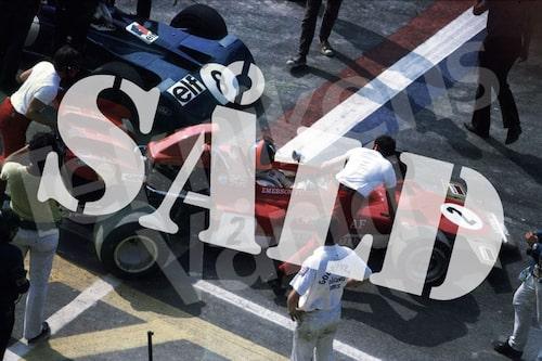 Bild 27. 1971. Emerson Fittipaldi i en Lotus 72 är angelägen om att komma ut på banan före konkurrenten Jackie Stewart i sin Tyrrell 001. Mått 50 x 35 cm. Pris: 100 kr.