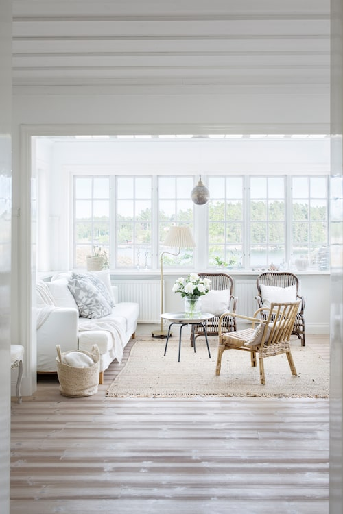 """Den här verandan kallar Marie för """"ren ljusterapi"""". Armaturerna i huset är generellt sparsmakade och lågmälda, för att inte störa skådespelet utanför. Stolar och fåtöljer i rotting finns i hela huset, flera är från Ikeas popup-kollektioner, möbler som får flytta ut och in."""