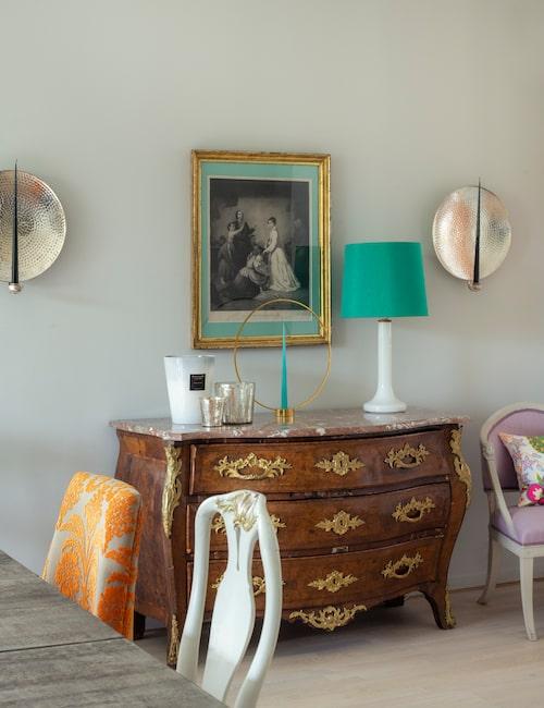Rokokobyrå med turkost tema: Klongljusstake, retrolampa och antikt omramat kopparstick.