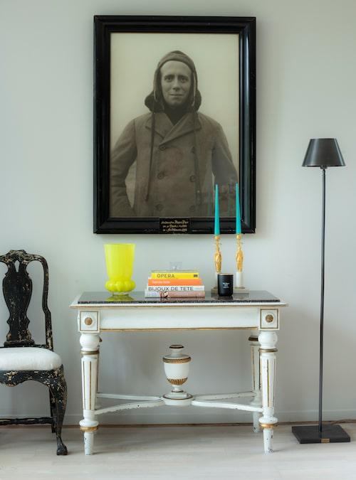 Stilmöte i svartvitt. Porfyrbordet är 1800-tal, stolen rokoko och ljusstakarna empire. Foto på släkting, tidigt 1900-tal. Gul vas av Anna Kraitz, Målerås.