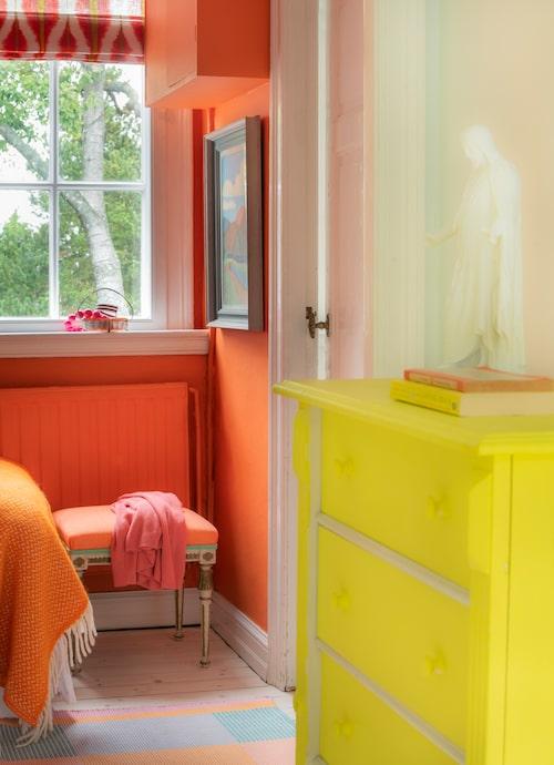 Den orange sovrumsfärgen är från 60-talet. Nu matchad av orangeklädd, gustaviansk taburett och uppsydda hissgardiner i spanskt tyg. Byrån har målats knallgul i kulören Lemon cake från Farrow & Ball.