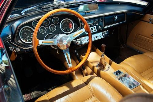 Cockpiten har alla inslag som vi förväntar oss av en Grand Turismo från 1960-talet. Svartlackerad panel, ett myller av mätare och kromade plåtdelar, en tunn träratt och lyxig skinninredning.