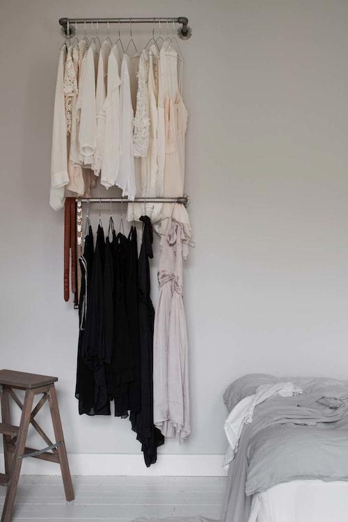 Dekorativ compact living-lösning: Stänger från Granit med färgsorterade kläder direkt på väggen. Ikeapallen är betsad med grå regndis-lasyr, grå linnelakan, H&M Home.