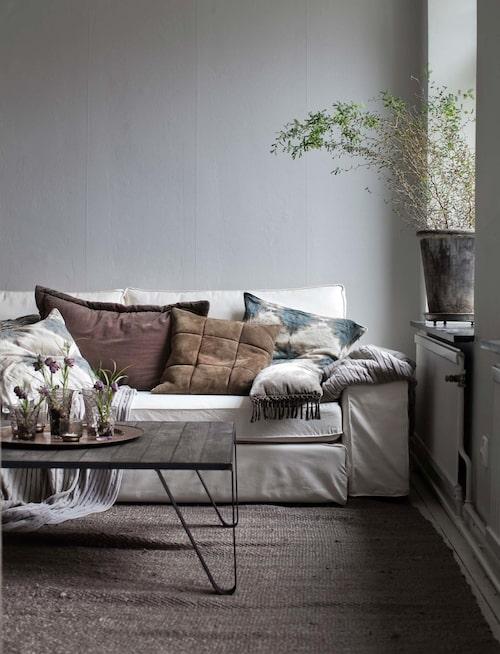 Soffan är Kivik från Ikea, kuddar och matta från Tine K home. Soffbord, Jonas smide på Öckerö. Små kungsliljor står i glaslyktor från Tine K home. Grå plädar, Ralph Lauren.