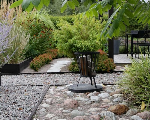 Brunmålat trä bildar kantgräns mellan grus av olika dimensioner och en yta med naturligt rundade stenar.