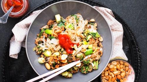 Strö jordnötter över färsnudlarna och servera med chilisås.
