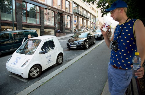 En ung Erik Wedberg studerar den norska elbilen Buddy på en gata i Oslo.