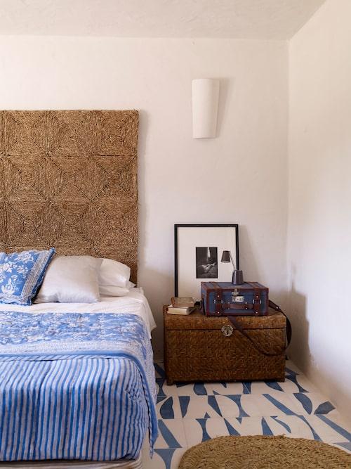 Det blå temat återfinns i alla sovrum. Här bildar en sjögräsmatta en annorlunda sänggavel. Rottingkistan lämnades kvar i huset av de tidigare ägarna. Golv, Popham design.