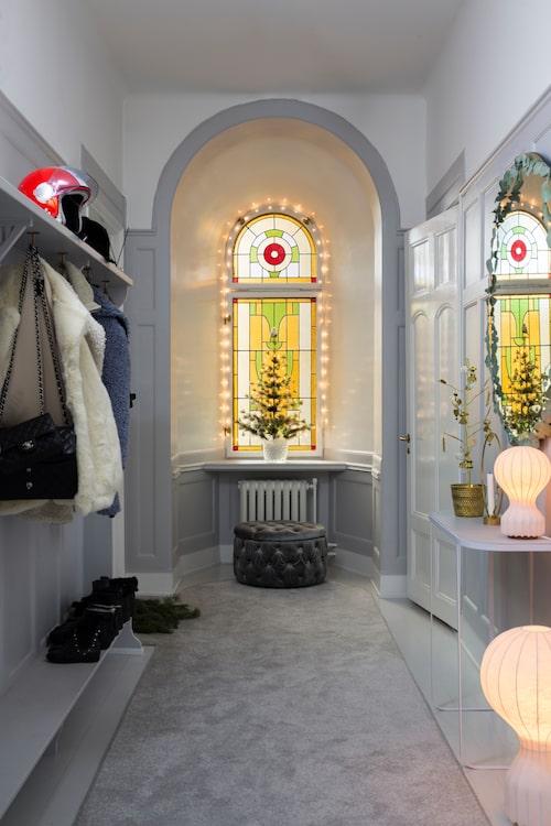 """Det vackra blyinfattade fönstret i hallen får lite extra glans av en ljusslinga så här till jul. Liten julgran i plast från Ikea. Spegel, puff och sideboard från Sleepo, lampor, Flos, ljusstake, Skultuna och guldkruka, Svenskt tenn. Mattan är måttbeställd från Matt-tema. """"Den är gjord av majs och plast, alla fläckar går bort med varmt vatten"""", säger Lisa."""
