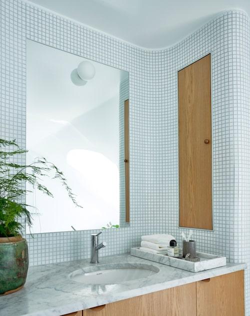 Badrummet rymmer hantverkskonst på hög nivå. Väggen har mjuka runda hörn och är klädd med mosaik samt hyser ett inbyggt och platsbyggt förvaringsskåp i ek. En integrerad spegel är införlivad med mosaiken och lyses upp av en armatur som är fastsatt på glaset. Dessutom en marmorskiva som sågats så att de runda mjuka hörnen passar perfekt med väggen. Kruka, 2900kr, Walles&Walles, växten är en fjädersparris, bricka av carraramarmor.