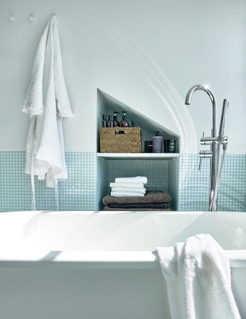 Nisch med förvaring. Varje utrymme har arkitekten Måns Tham försökt att utnyttja. Allt man behöver när man tar ett bad – tvål, schampo och handdukar – finns på armlängds avstånd. Den övre delen av förvaringsnischen följer innertakets lutning som i sin tur följer husets yttertak. Mosaiken möter vitmålad vägg och tak.