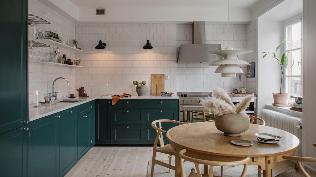 Här har man valt bort överskåp för att få en luftigare, lite restaurangaktig känsla. Det vita kaklet och den vägghängda glashållaren från Kitchenlab förstärker intrycket. Vintagebordet av Børge Mogensen och stolarna av Hans J Wegner adderar värme och hemtrevnad till det stilrena köket. Köksinredningen är byggd av stommar från Ikea och fronter från Järfälla kök. Kyl, frys och diskmaskin är inbyggda och göms bakom skåpfronter. Spis från Smeg, fläktkåpa, Ikea, marmorskiva, Stenfirma Bror Törner. Väggarmaturen är Mantis från DCW Éditions Paris. taklampa, Louis Poulsen.Keramikvas från 101 Cph, assietter från Blackballoon/Tell me more.