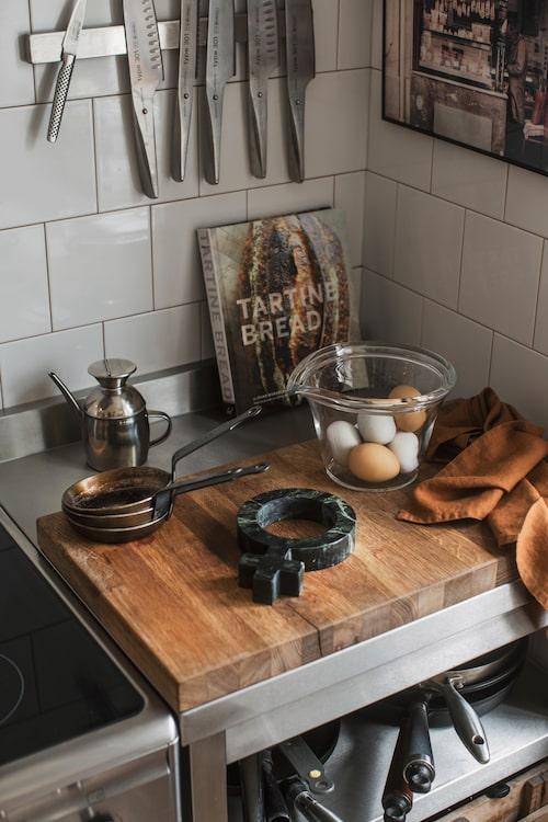 Kockens hörna med en rostfri bänk och tillhörande skärbräda har ägaren Carl-Johan gjort själv. På skärbrädan ligger ett underlägg i grön marmor från Oscar Lundgren. Oljekaret kommer från Paris och kökshandduken i färgen Amber från Blackballoon/Tell me more. Magnetisk knivskena, Ikea.